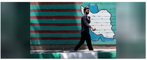 A man walks past the mural showing U.S. flag with barbed wire in Tebran, Iran June 25, 2019. Nazanin Tabatabaee/Nazanin Ta:barabaeeWest Asia News Agency via REUTERS